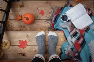 Feet in the socks, cup of coffee, blanket and a pumpkin.