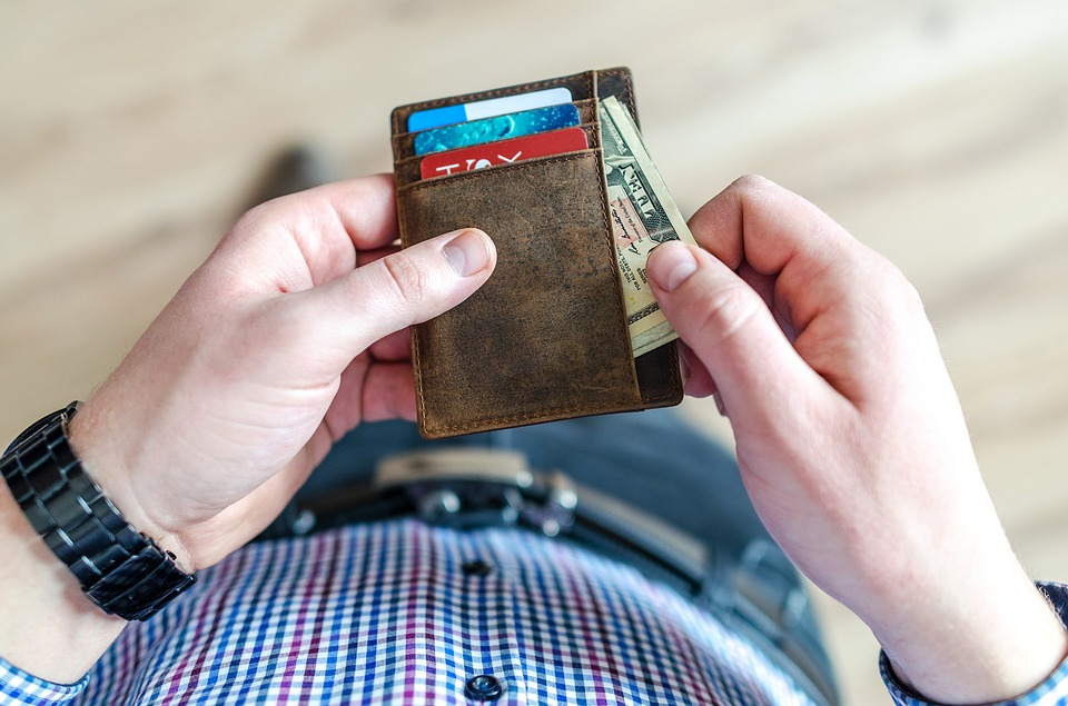Man looking at his wallet, preparing to pay for moving prices Miami.