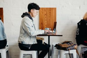 Man in cafe with working on laptop