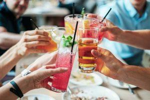 Manos con diferentes bebidas.