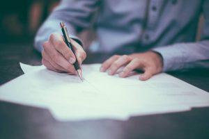 A man signing paperwork