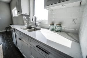 White kitchen with counter top and sink.