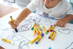 Child drawing with crayons.
