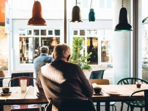 Packing guide for seniors- a senior sitting in a coffee house