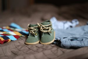 A pair of baby shoes and some clothes in the background.