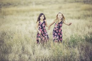 Two girls in dresses running in a field.