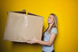A girl carrying a large moving box