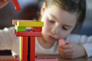Girl playing with different colored blocks.