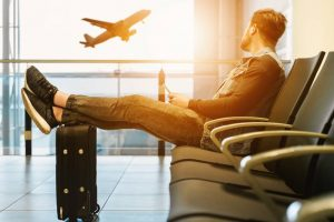 man sitting on chair looking at airplane