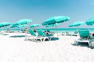 white and green loungers on the beach