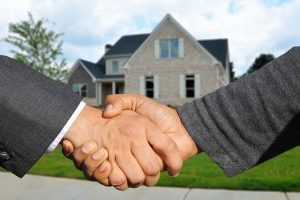 Shaking hands in front of a home