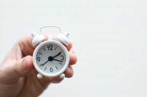 A person holding a small white clock
