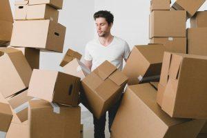 Man between a bunc of movign boxes