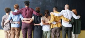 8 people hugging as symbol of cultural diversity and one of the reasons why you should move to Miami from Fort Lauderdale
