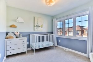 A nice nursery room with bed, dresser, and huge windows through which the houses are seen.