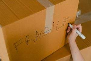 A person writing FRAGILE on a moving box