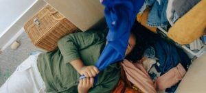 A girl lying covered with clothes