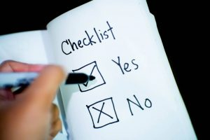 Person checking the yes box on the checklist
